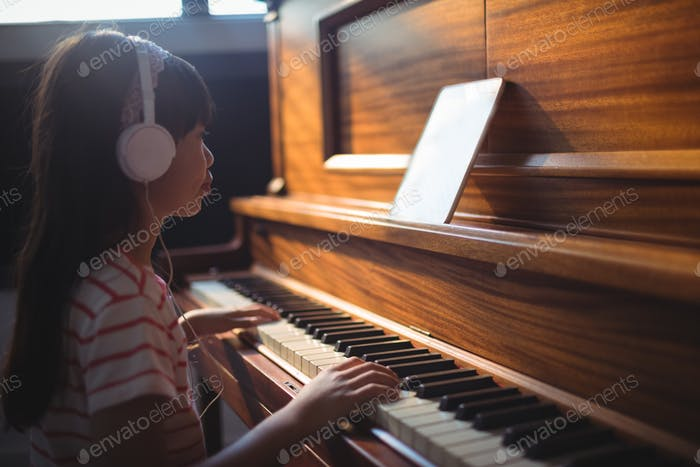 Girl looking at digital tablet while practicing piano in classroom