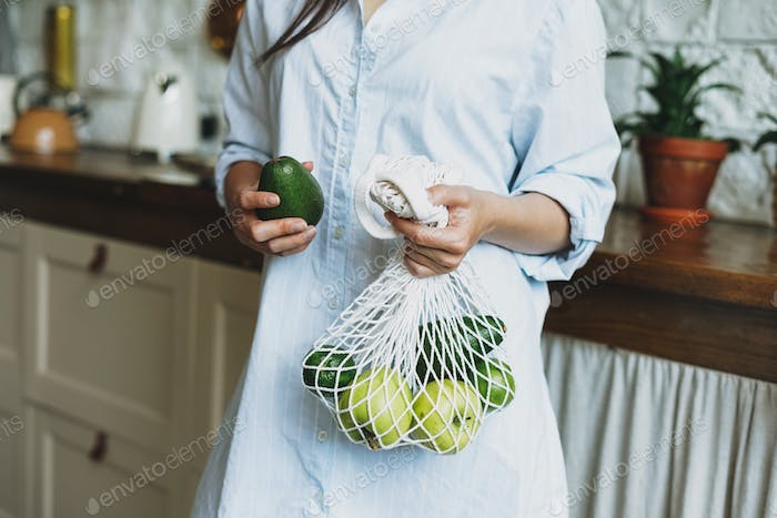 Young woman in shirt hold knitted rag bag shop with avocado and green apples in hands