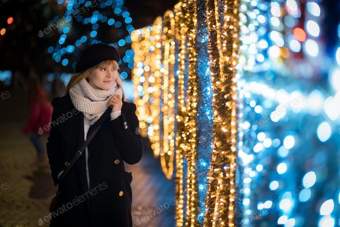 Young woman walking along illuminated alley during Christmas