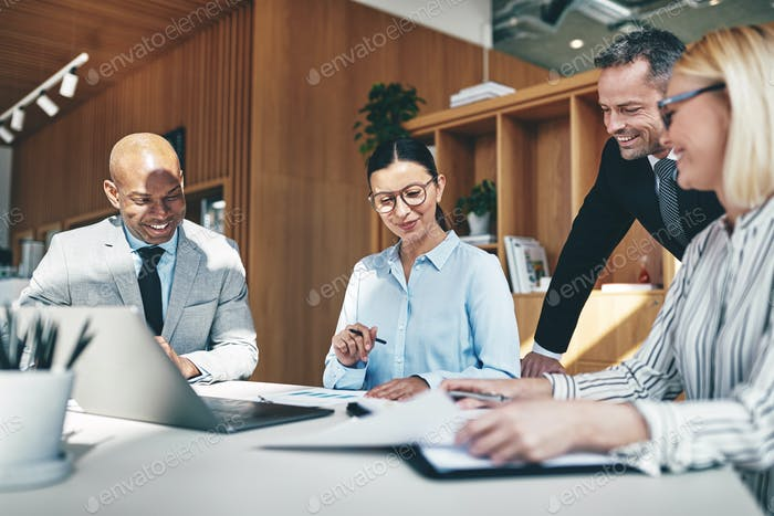 Laughing businesspeople going over paperwork together during an office meeeting