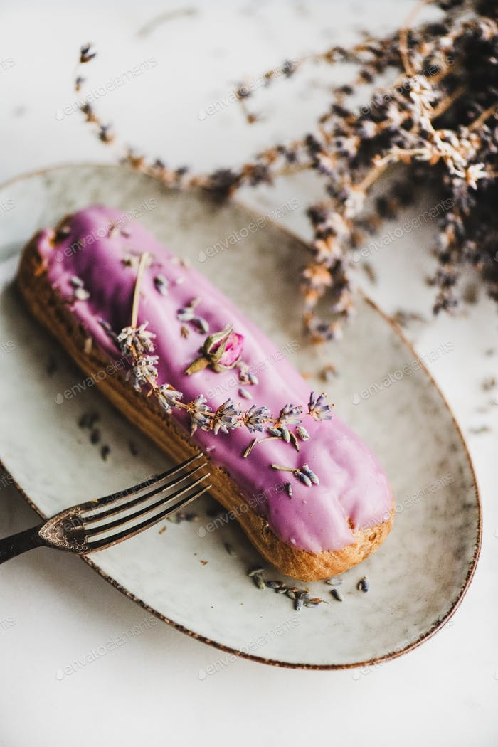 Lavender eclair decorated with purple flowers on oval plate