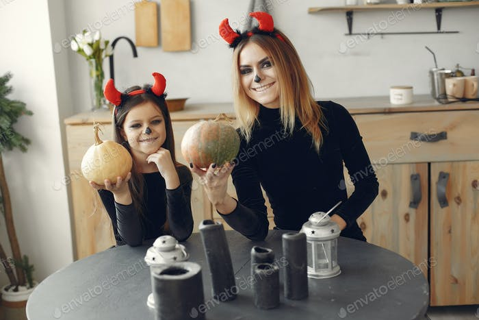 Mother with daughter in a halloween costume and makeup
