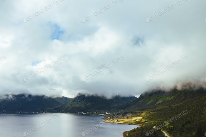 Clouds covering mountains by lake