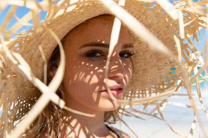 Young woman with straw hat at the beach