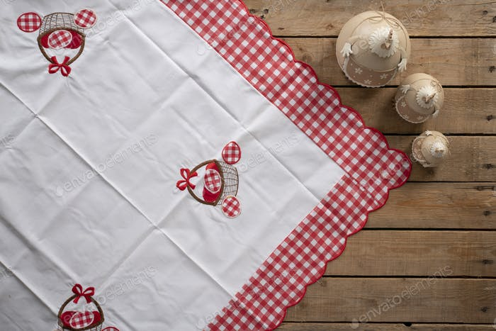 Easter background with a tablecloth and three different shape of decorative chickens