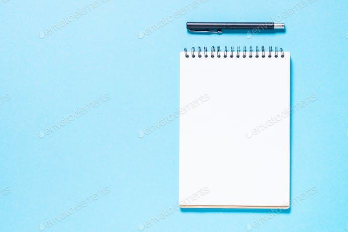 Cuaderno y bolígrafo sobre Fondo azul