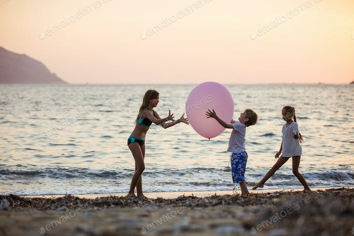 Children playing with huge pink balloon on beach at sunset