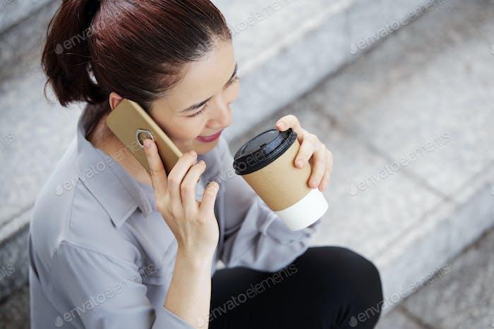 Cheerful businesswoman talking on phone