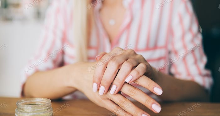 Woman applying moisturizing cream on hands