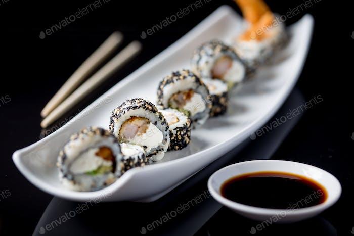 Sushi-Rollen auf weißem Teller. Schwarzer Hintergrund