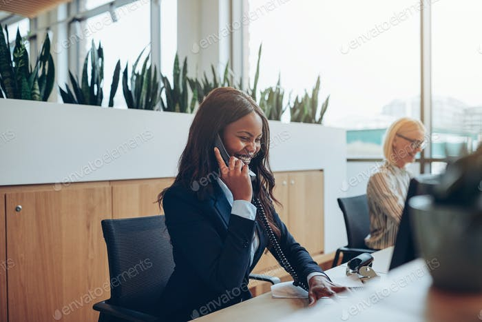 Laughing African American businesswoman talking on an office phone