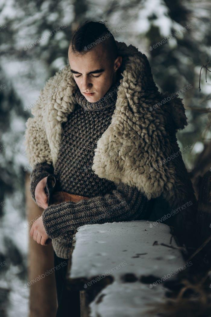 Antike Wikinger Krieger mit Stahlaxt posiert in der Nähe von Holzhütte im skandinavischen Wald