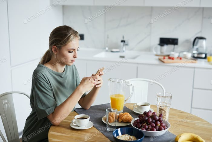 Young attractive woman using smartphone while having breakfast