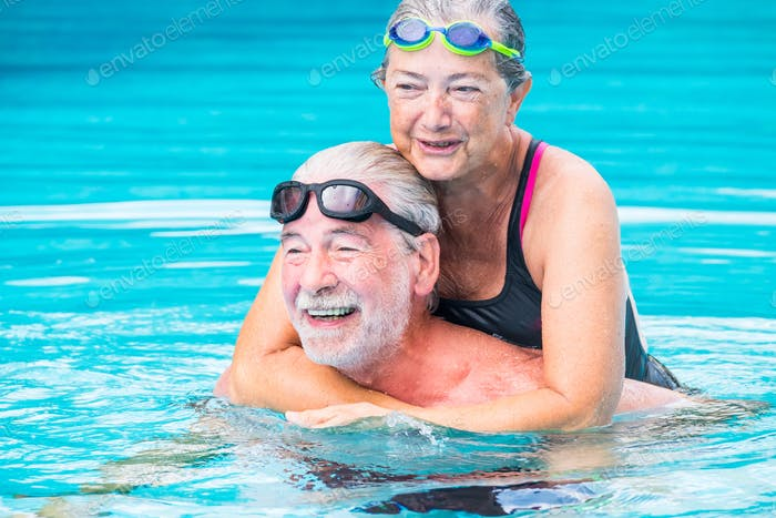 two pensioners or mature old people enjoying summer and vacations in the swimming together