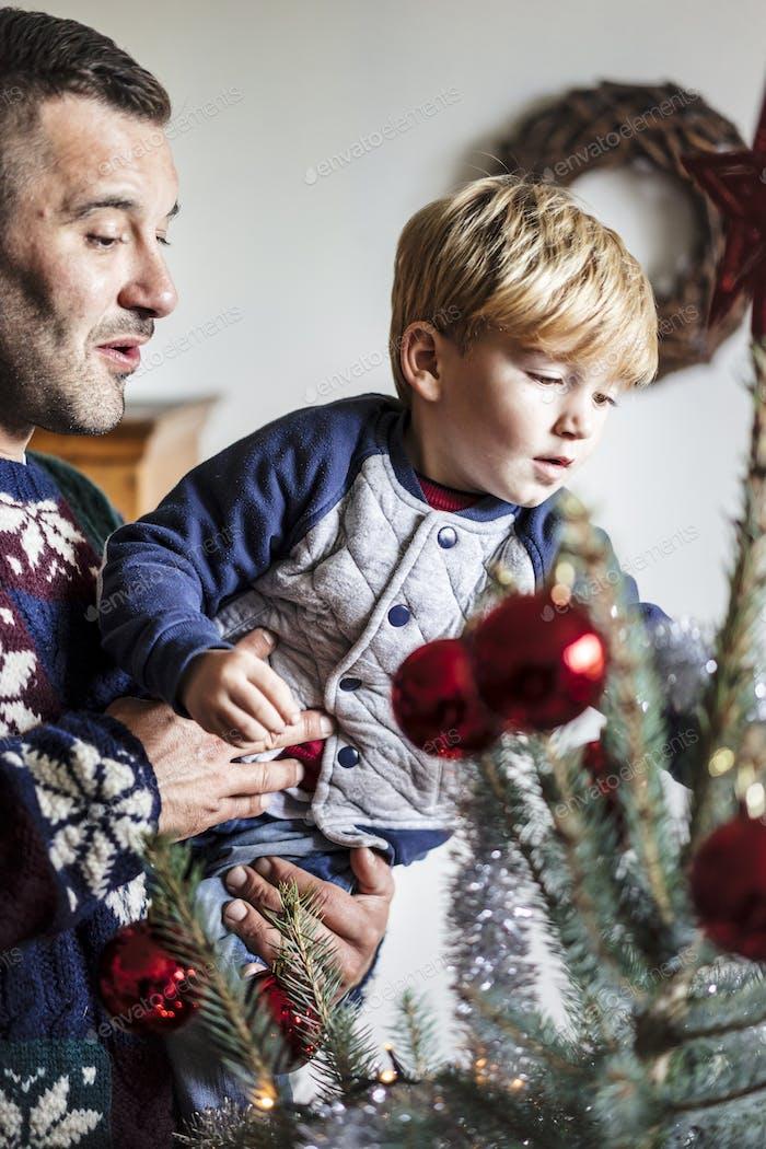 glückliche Familie mit einem kleinen Kind schmücken einen Weihnachtsbaum bei h