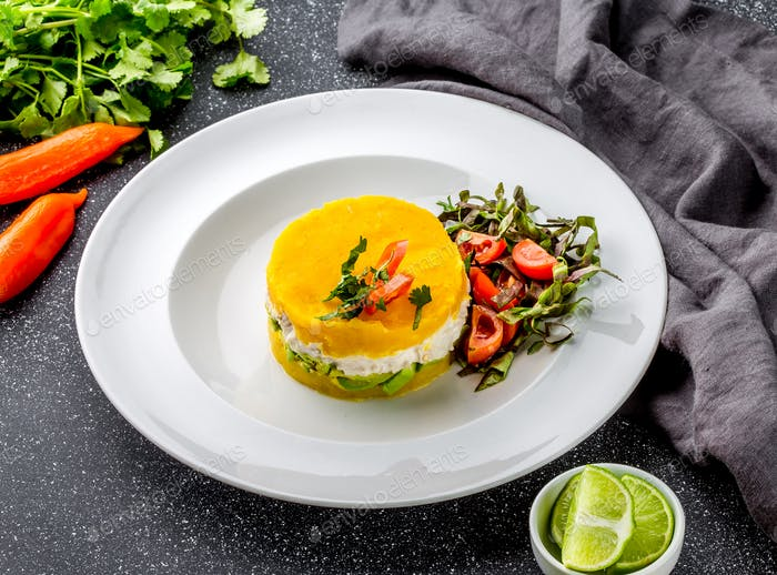 Traditional peruvian dish CAUSA from yellow potato, chicken, avocado on white plate.