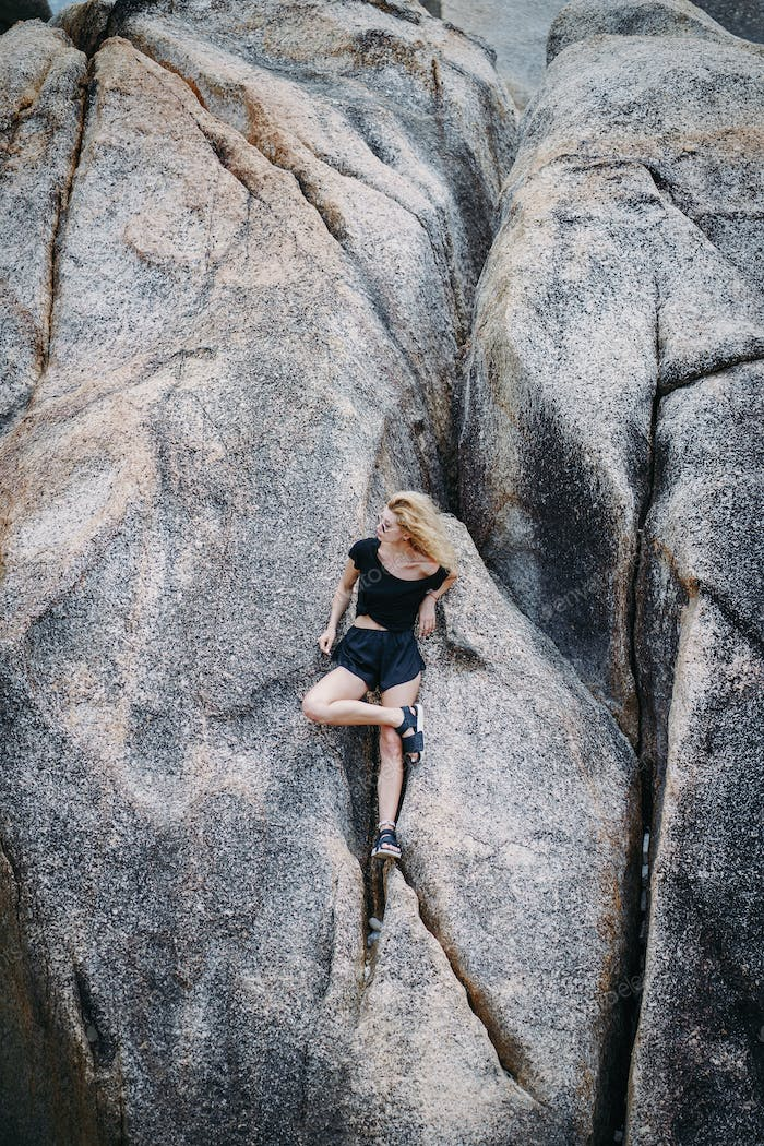 blonde girl sitting on a rock formation