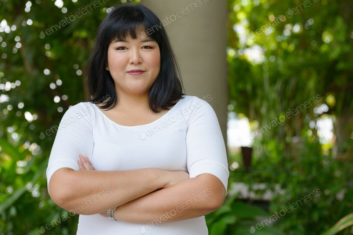 Young beautiful overweight Asian woman at the park