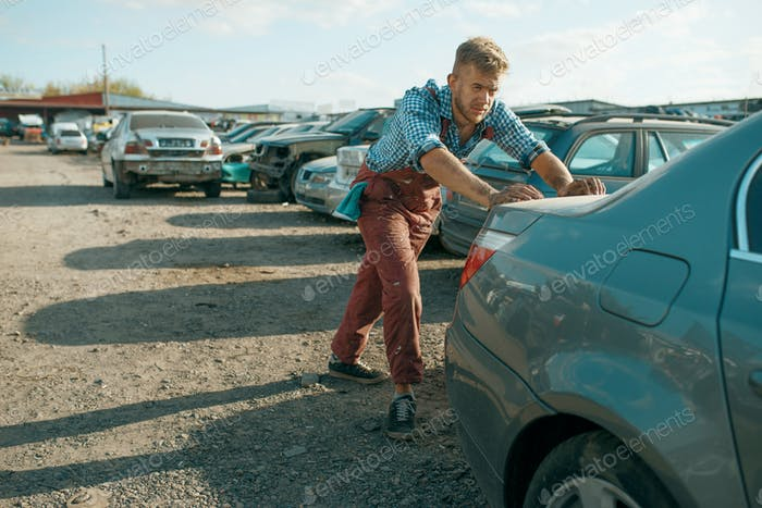 Male mechanic pushing the car on junkyard