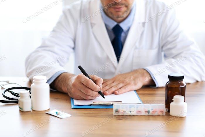 Nahaufnahme eines Arztes, der ein Rezept schreibt