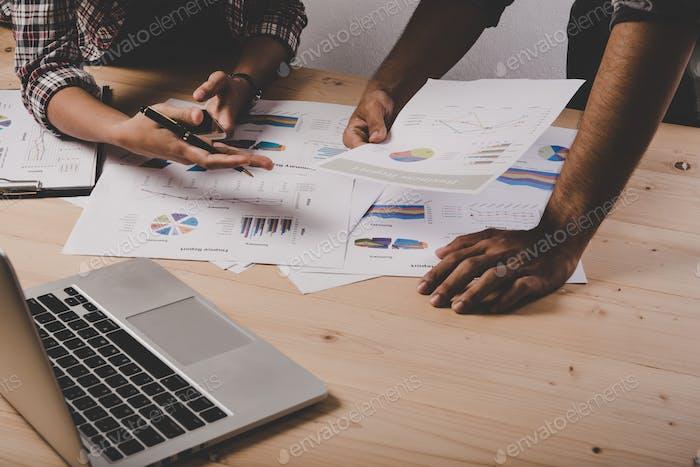 Nahaufnahme von Geschäftsleuten, die während der Diskussion bei Besprechungen mit Geschäftsdokumenten arbeiten.