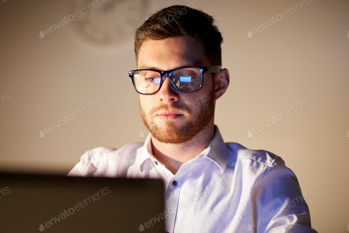 businessman in glasses with laptop at night office