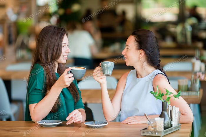Happy young women with cups of coffee at outdoor cafe. Communication and friendship concept