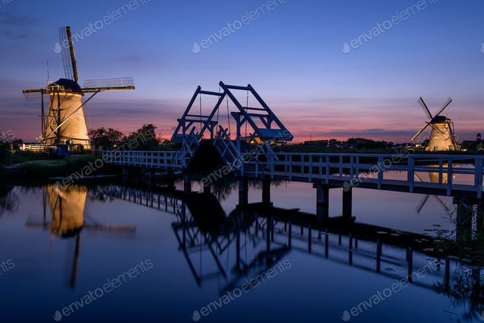 Windmills and a bridge illuminated at dusk