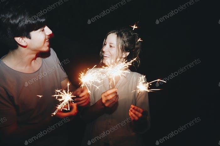 Caucasian Mann und Frau Paar spielen mit Wunderkerzen Feier und festliches Party-Konzept