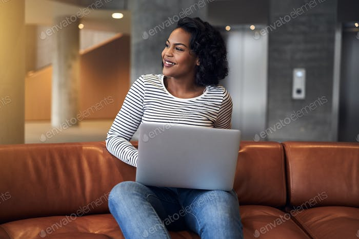 Smiling young African university student working online on campus