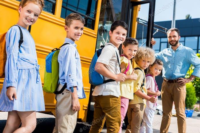 queue of pupils standing near school bus with teacher