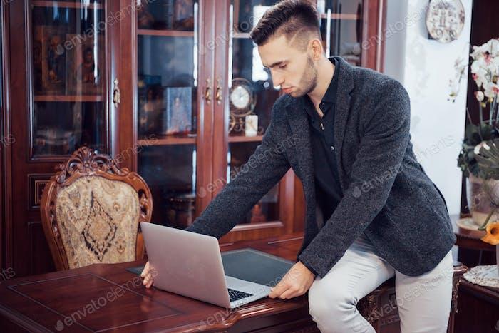Confident handsome businessman sitting in luxury interior