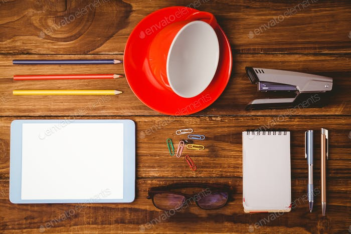 Tablet next to cup and notepad on wooden table