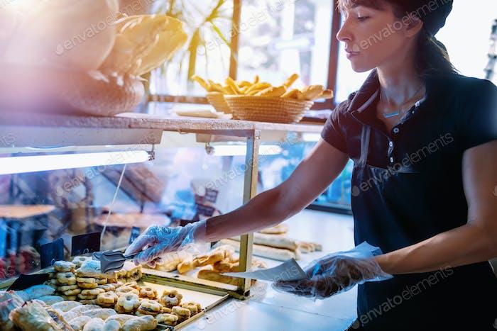 Female Shop Assistant Arrange Pastry In Bakery Shop Window