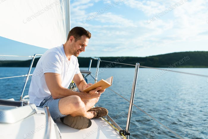 Man Reading Book Sitting On Yacht Deck Sailing In Sea
