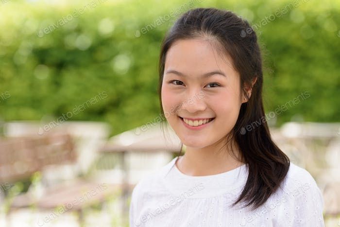 Face of happy young beautiful Asian woman smiling at the coffee shop outdoors