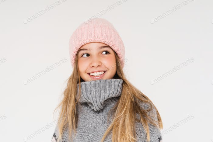 Cute smiling teenage girl in pink knitted hat and cozy gray poncho