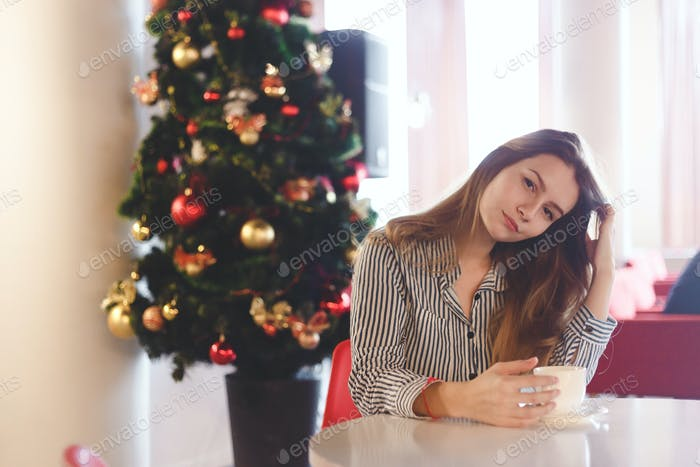 Girl drinking coffee sitting near a Christmas tree in cafe