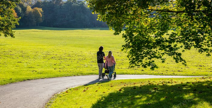 City park, Munich, Germany. View of a young couple with a baby cart walking on a path
