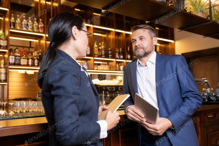 Two owners of luxurious restaurant interacting by bar counter