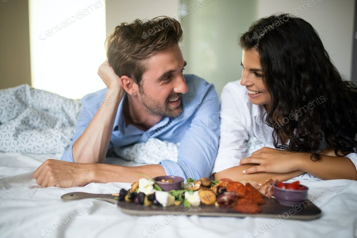 Romantic happy couple having breakfast in bed