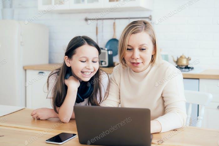 Mama und Tochter sitzen in der Küche und reden und lachen auf den Laptop-Bildschirm schauen.
