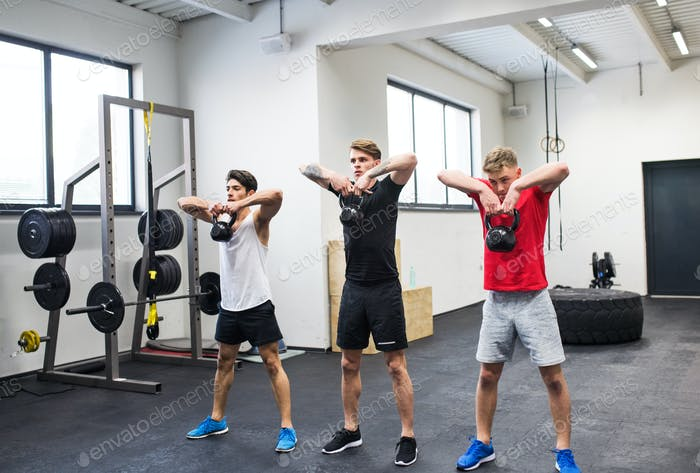 Three young men in gym doing kettlebell swings.