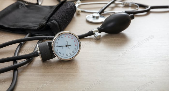 Medical stethoscope and sphygmomanometer on wooden background