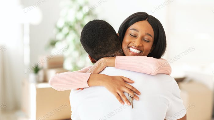 Happy black lady holding house key and embracing her boyfriend in their apartment, copy space