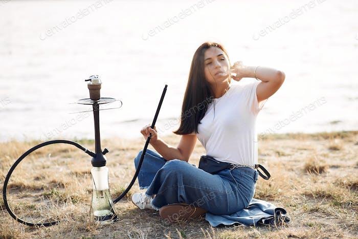 Frau halten Pfeife Rauchen Shisha allein außerhalb