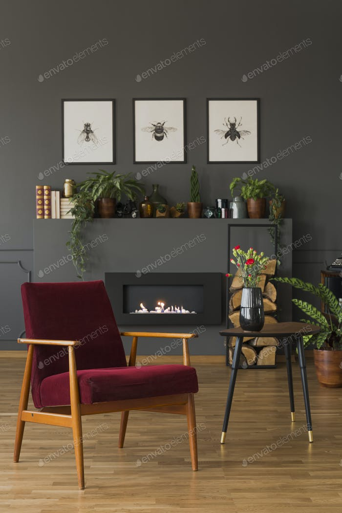 Red wooden armchair next to table with flowers in dark living ro