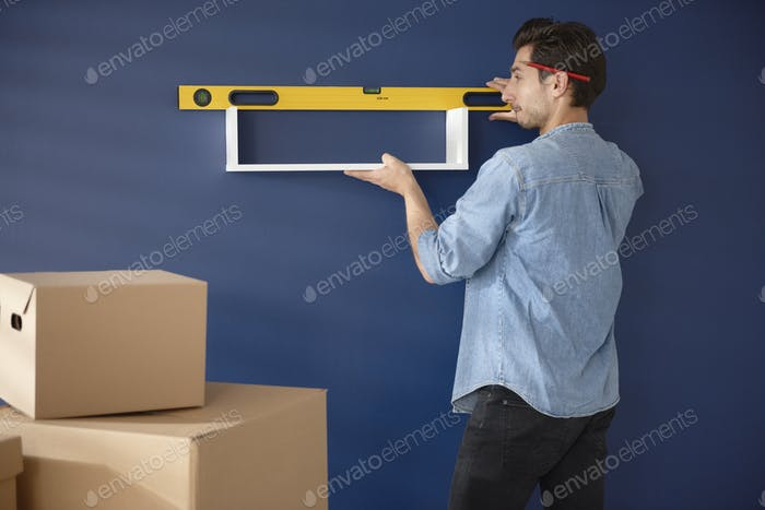 Man checking if the shelf in perfectly horizontal