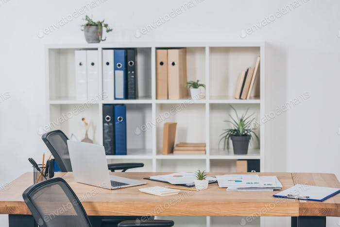 table in office with laptop, documents, chairs and bookcase fo folders on background