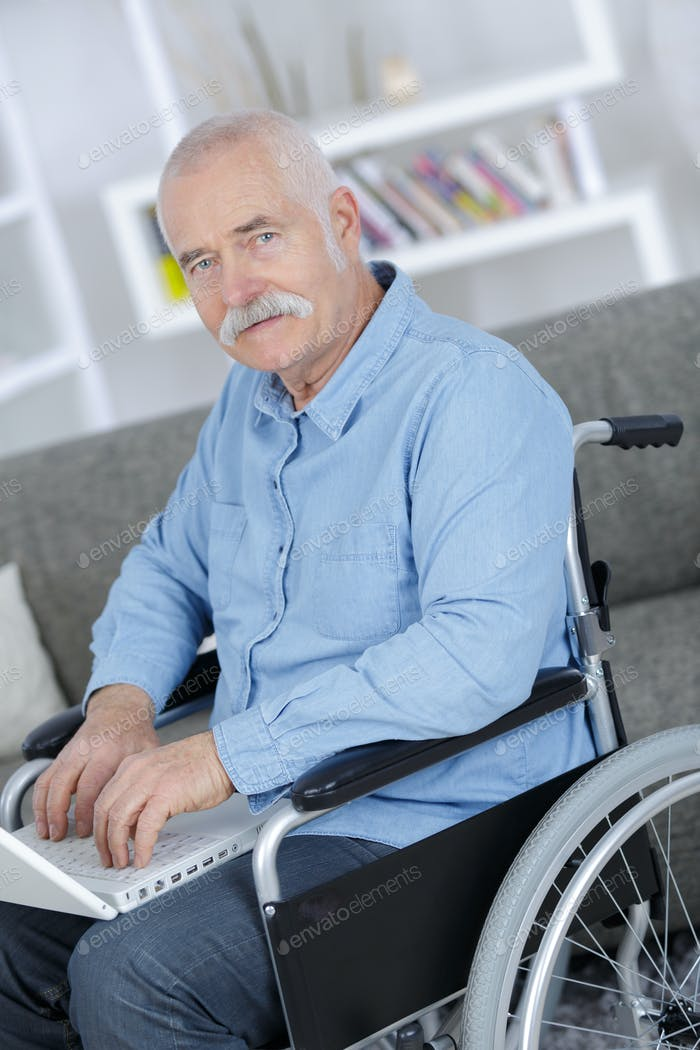 mature businessman in a wheelchair working on a laptop